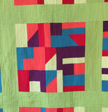 close up of quilt block in solid colours with matchstick quilting.