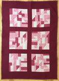 quilt with randomly pieced blocks in shades of pink with spiral quilting.
