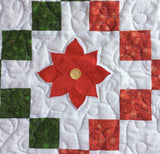 close up of poinsettia applique on quilted table runner.