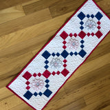 pink and blue table runner with embroidered flowers.
