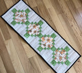 table runner with green accent fabric.