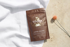 Packet of Tonika's Coffee Creamer on beige tile and white cloth with orange dried flower