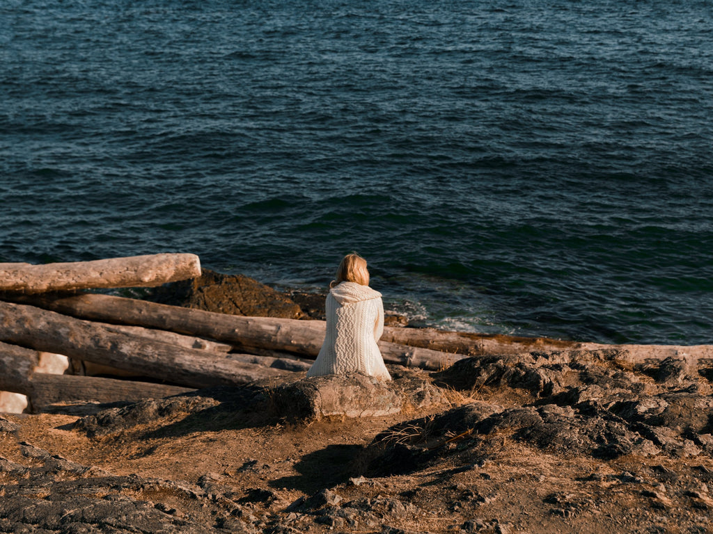 A person sitting  on a pile of logs in front of a British Columbia seashore.
