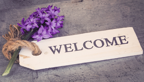 Image says 'Welcome' with a purple flower