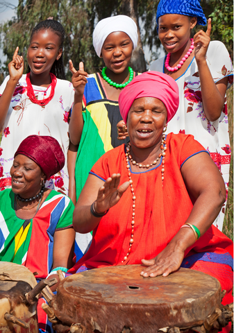 Group of women singing and beating a drum