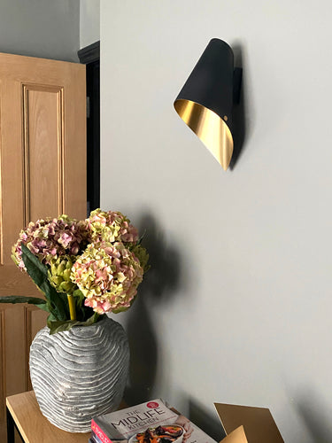 Black and brass wall light over a console table