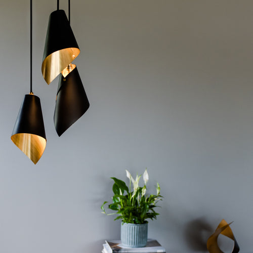 brushed brass and black modern pendant light over side table