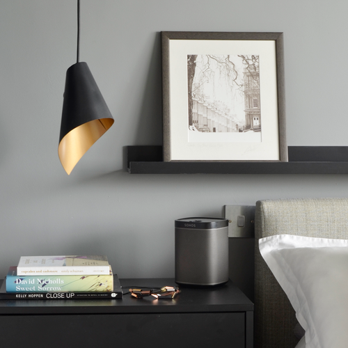 single pendant light in gold & black next to bedside