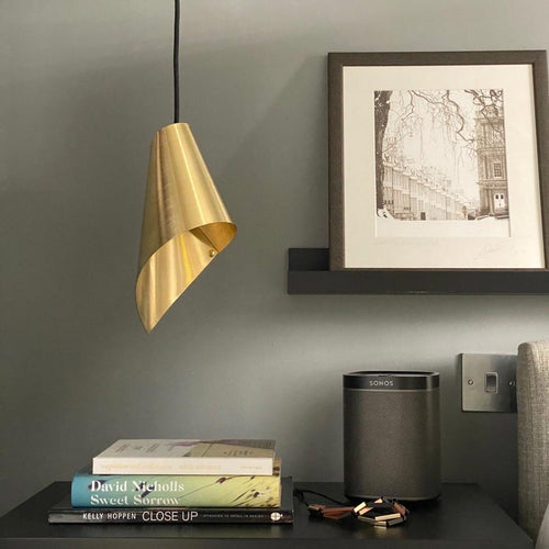 brushed brass modern pendant light over bedside table