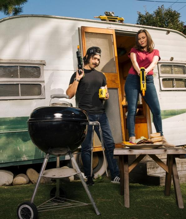 Man and woman with Bug-A-Salt guns in front of trailer