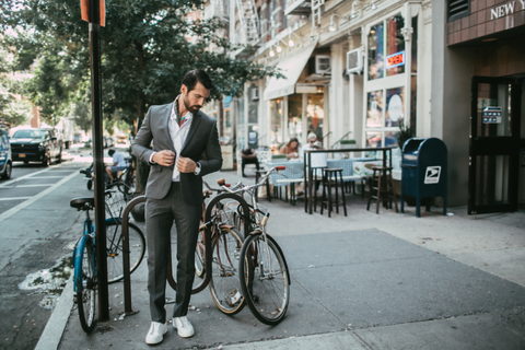 Man in GQ Business Suit in grey stands near a bicycle.