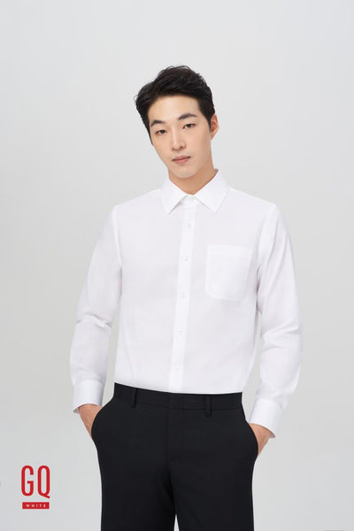 Man in GQWhite men's dress shirt and black pants stands with his hands in his pockets.