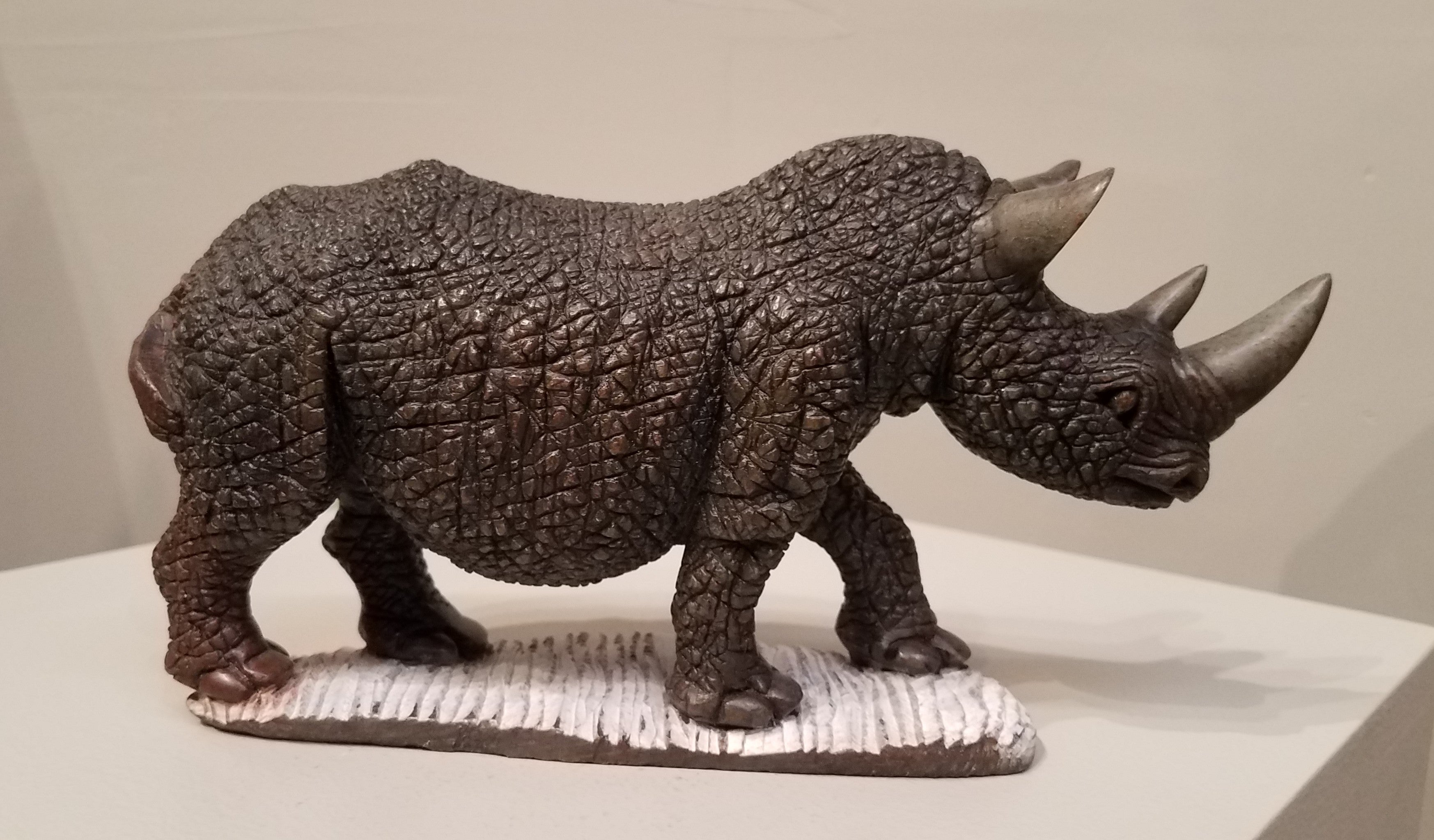 Rhino sculpted from a single piece of serpentine stone, in Zimbabwe. It is a brownish color, with a textured, rough finish for the skin, just like a real rhino skin. The horns, ears, and toes are finely sanded and brought to a shine, and the base that the rhino is walking on is left unpolished, so it's left a greyish/whitish color. The contrast gives the impression that the rhino is walking on a natural, rough ground. The base and the rhino are sculpted from one piece of stone, they are not glued together.
