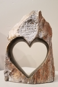 A sculpture of a heart, sculpted in Zimbabwe from a single piece of serpentine stone. The outer part is left completely natural, so it just looks like a regular rock, but out of that rock, and within the middle area, is sculpted a heart. That inner area of the stone, forming the heart, is finely sanded, and polished, bringing out its greenish/brownish colors.