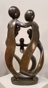 Loving Family sculpture, in abstract form, sculpted from a single piece of brownish serpentine stone, in Zimbabwe.