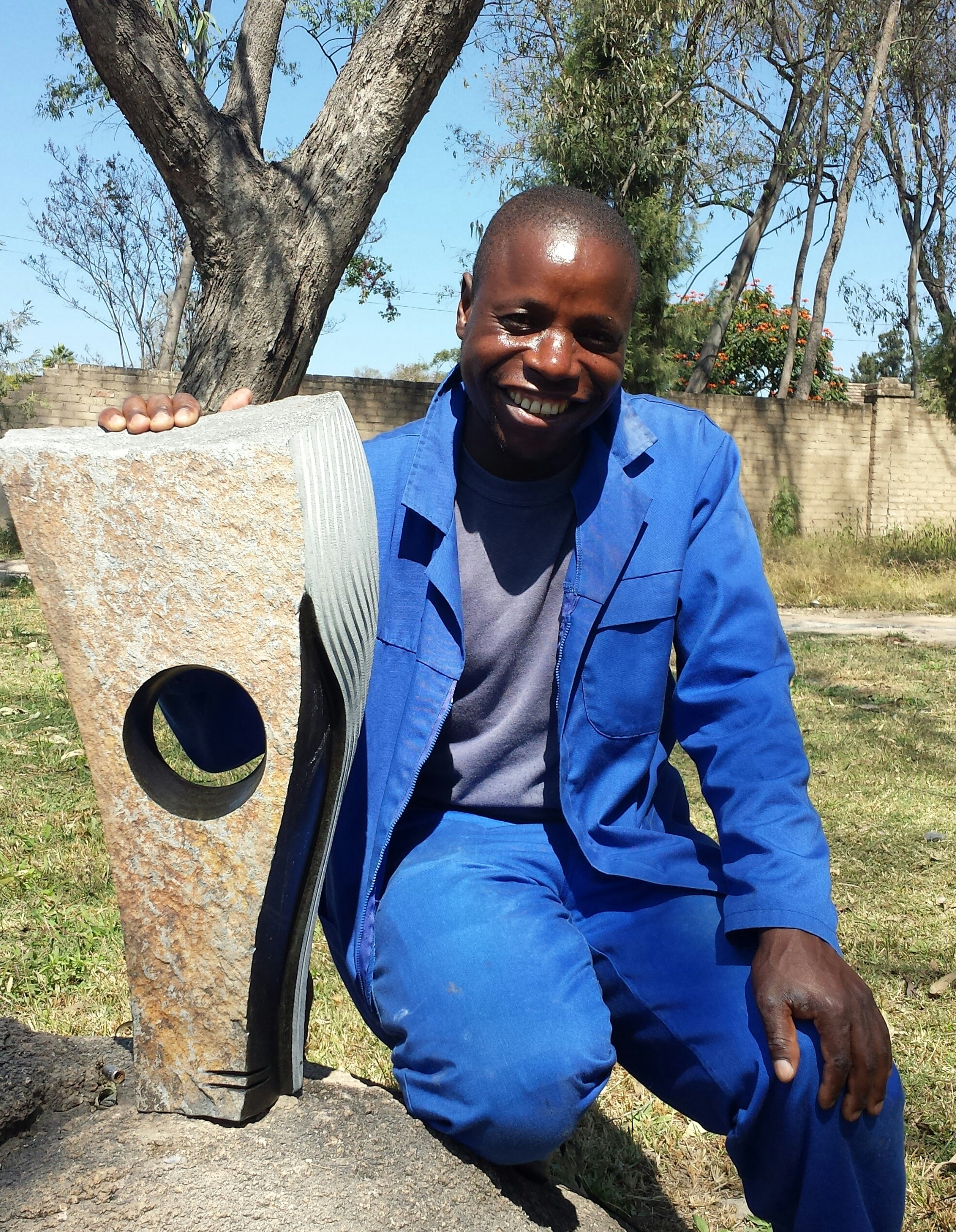 Artist Godfrey Matungamidze posing with sculpture.