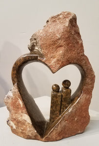 An abstract sculpture of a couple standing inside a heart, sculpted in Zimbabwe from a single piece of serpentine stone. The outer part is left completely natural, so it just looks like a regular rock, but out of that rock, and within the middle area, is sculpted a heart with two people standing to one side, inside the heart. The people, and the inside of the heart, are all polished, bringing out the greenish/brownish colors.