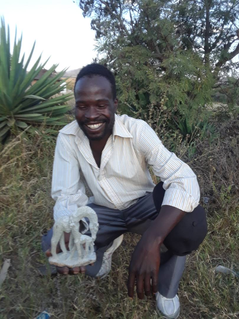 Photo of artist, Isheunesu Masimura, who sculpted the mother and calf giraffes from a single piece of serpentine stone.