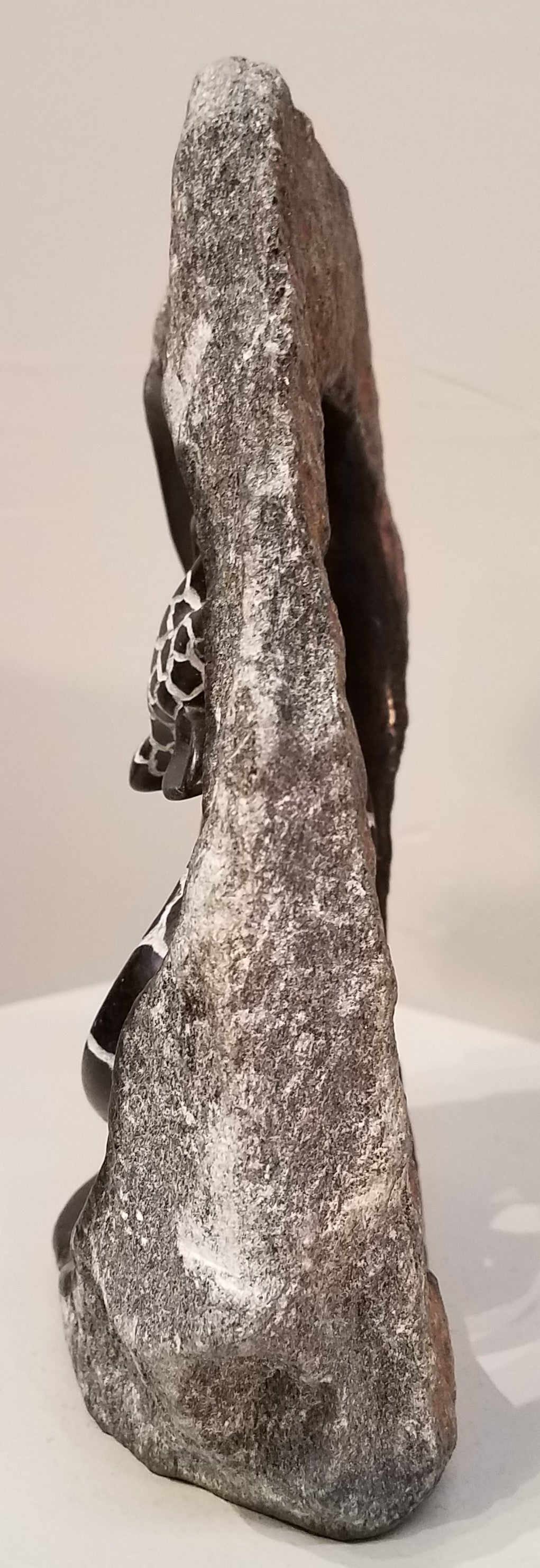 Abstract sculpture of kissing giraffes, within a circle of the untouched, and unpolished stone.  It was sculpted by hand from a single piece of serpentine stone, in Zimbabwe. The inner part of the circle, and giraffes, are completely polished, bringing out the dark brownish color of the stone. The pattern of the giraffes is etched out of the polished stone, leaving a contrasting greyish/whitish pattern