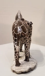 Beautiful mother giraffe tending to her calf was sculpted by hand from a single piece of serpentine stone, in Zimbabwe. The stone is a brownish color, and the pattern has been etched out of the polished stone, becoming a greyish/whitish color.