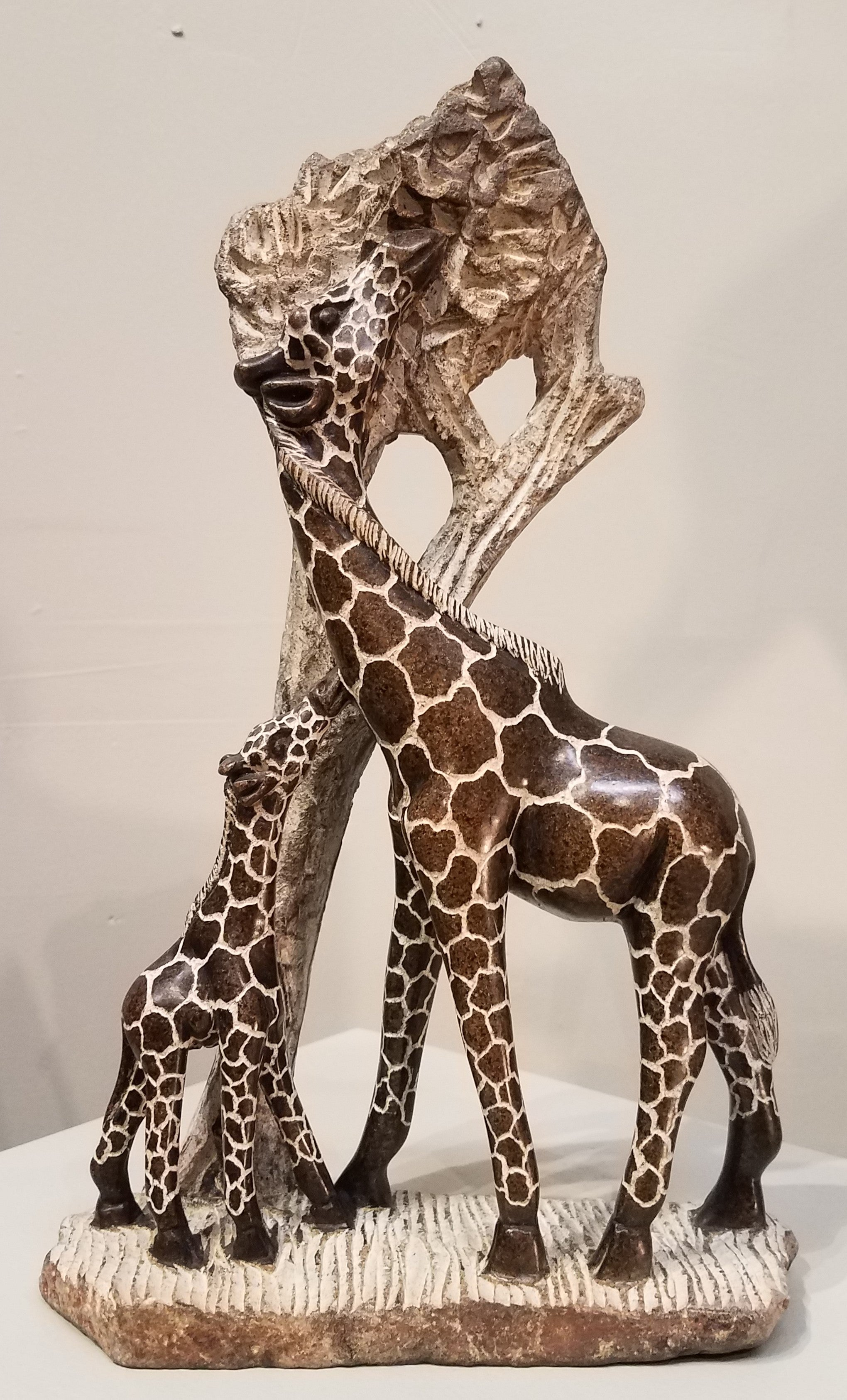 Beautiful mother giraffe with her calf was sculpted by hand from a single piece of serpentine stone, in Zimbabwe. The stone is brownish, with the patterns etched into the polished stone. The etched areas are greyish/whitish, as is the tree that they are eating from.