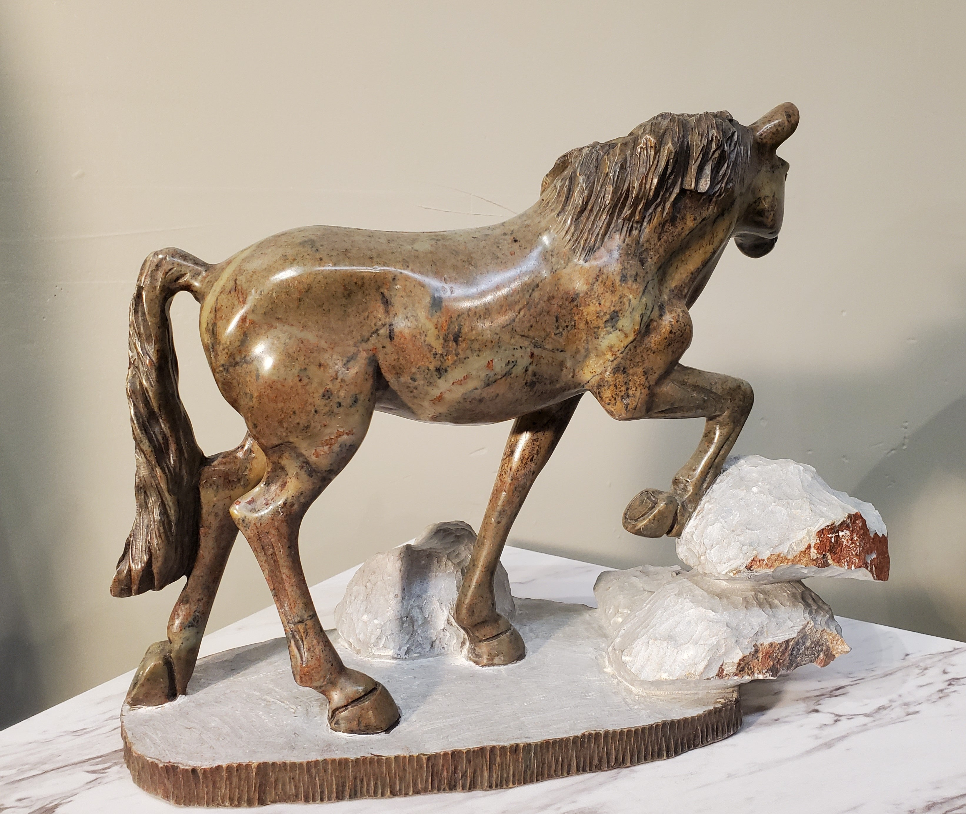 Beautiful realistic horse walking on a white piece of stone with rocks. Color Range: Brown, White, Black.