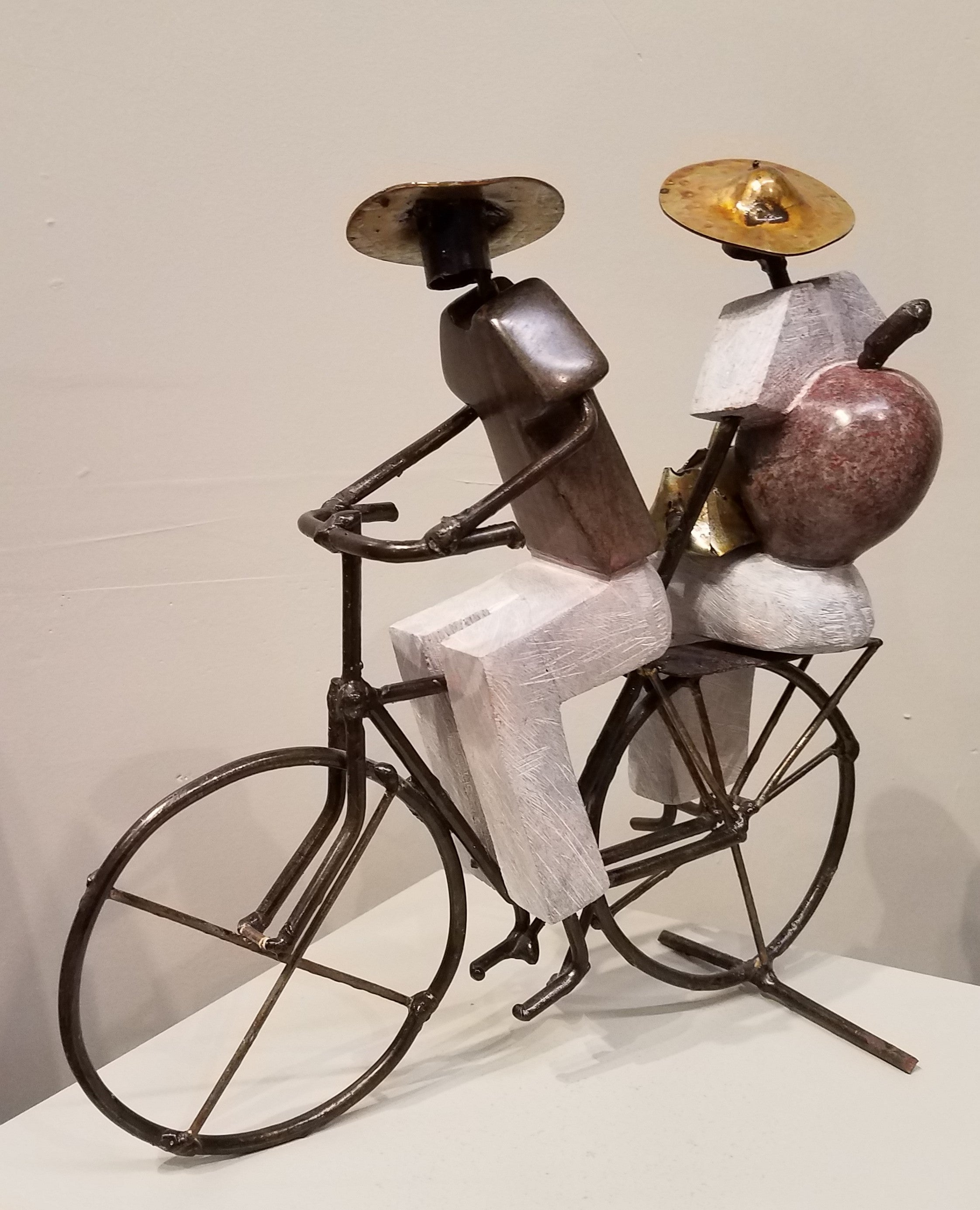 Sculpture of a man riding a bicycle, seated sideways behind him is his wife who has their baby tucked into a towel on her back, typical method in Zimbabwe. It was created from a combination of rapoko stone (a soft serpentine), and metal, in Zimbabwe. The people's bodies are sculpted from stone, and the arms, legs, heads, hats, and bicycle, are all metal, welded and soldered together.