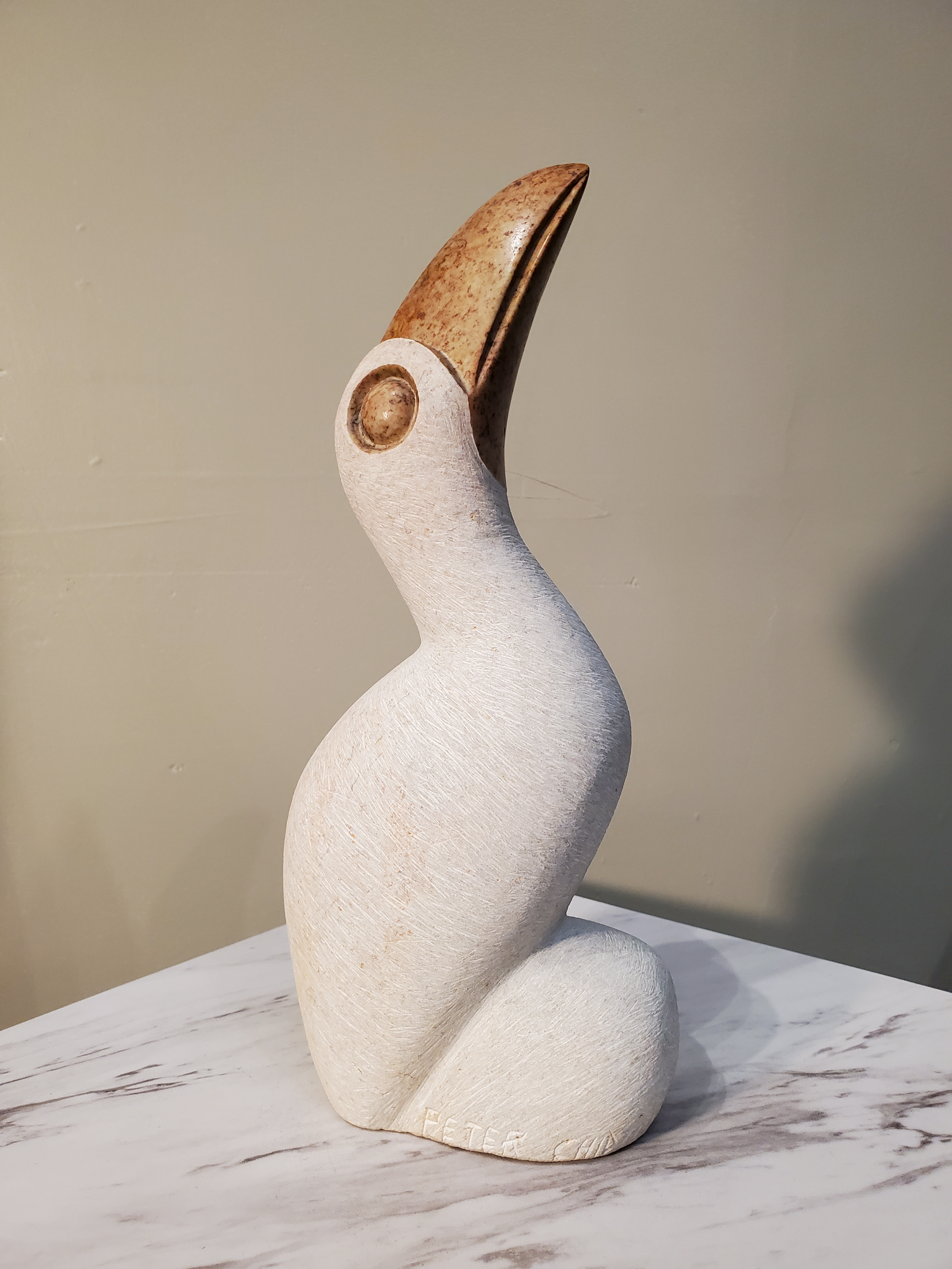 A beautiful perched white pelican looking inquisitively upward. This bird was sculpted from a single piece of opal stone. The white bird is accentuated by a bronze colored beak and eyes. Colors included: White, Bronze.