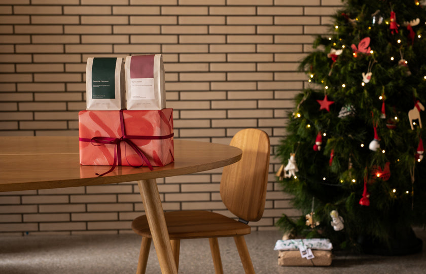 Christmas tree scene with gifts beneath the tree and on a table, including two bags of coffee.