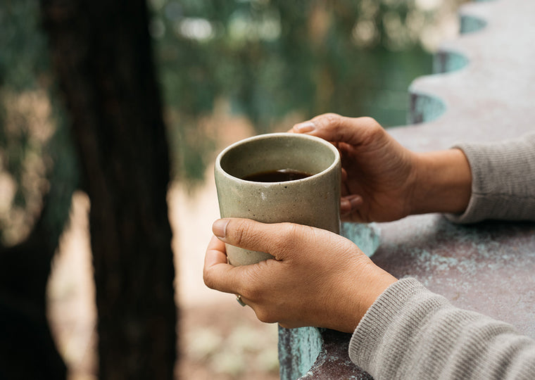 Two hands hold a cup of coffee at the edge of a balcony, person is facing eucalyptus trees.
