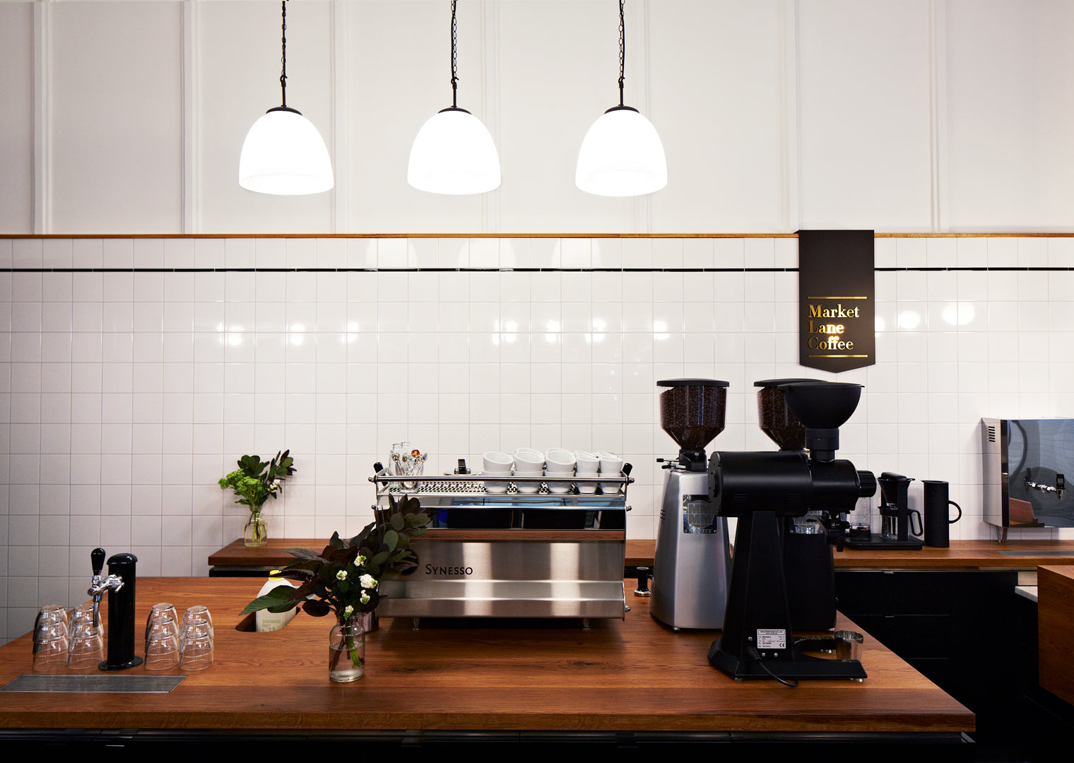A syneso coffee machine sitting on a timber benchtop at our cafe in the Dairy Hall of Queen Victoria Market.