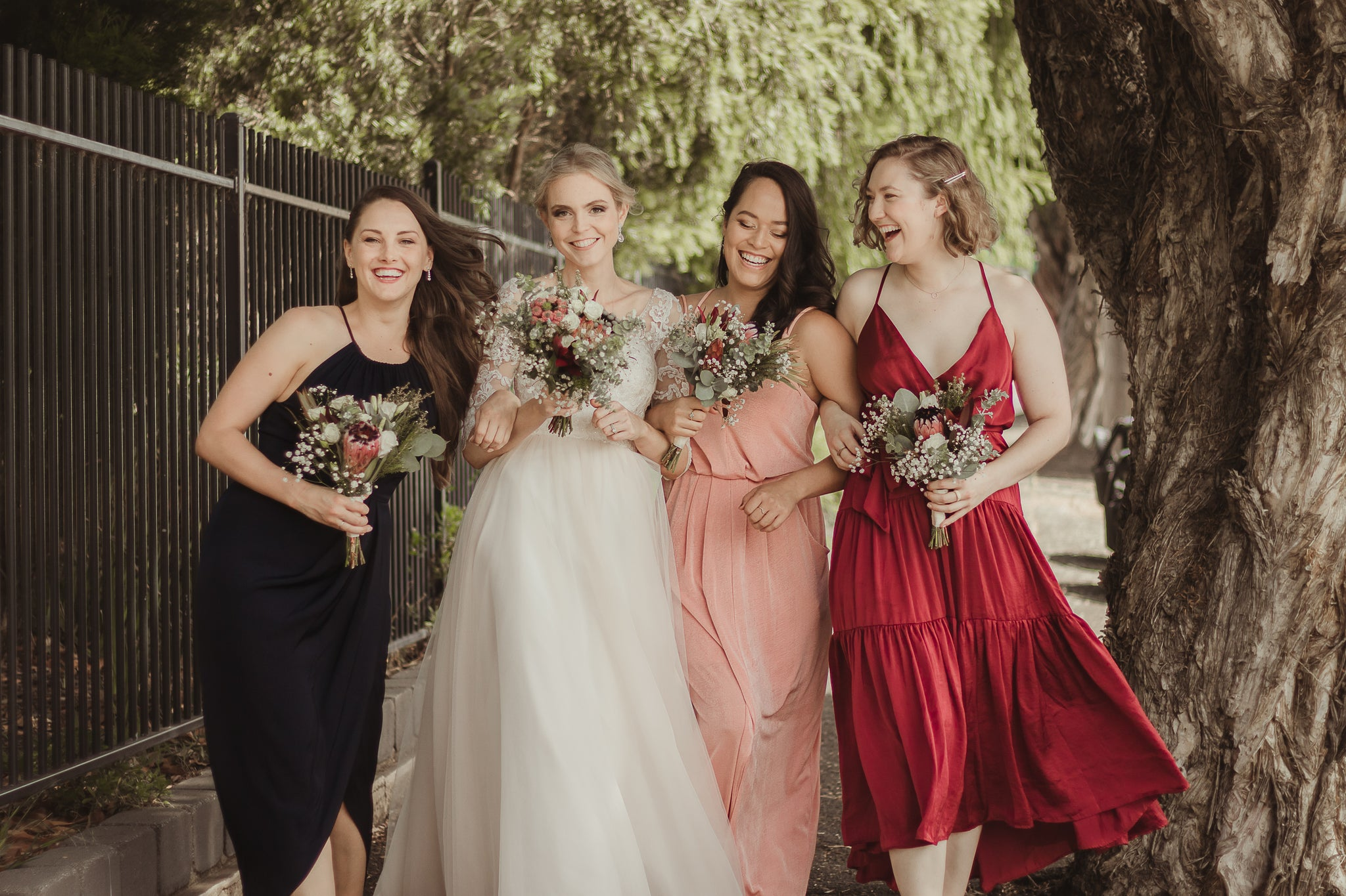 """Bride and three bridesmaids, wearing eclectic dresses in raspberry, pink, white and navy. Walking down the street linking arms and holding little bouquets of flowers, looks like a scene from """"Sex and The City"""". At Geelong Venue, The Warehouse."""