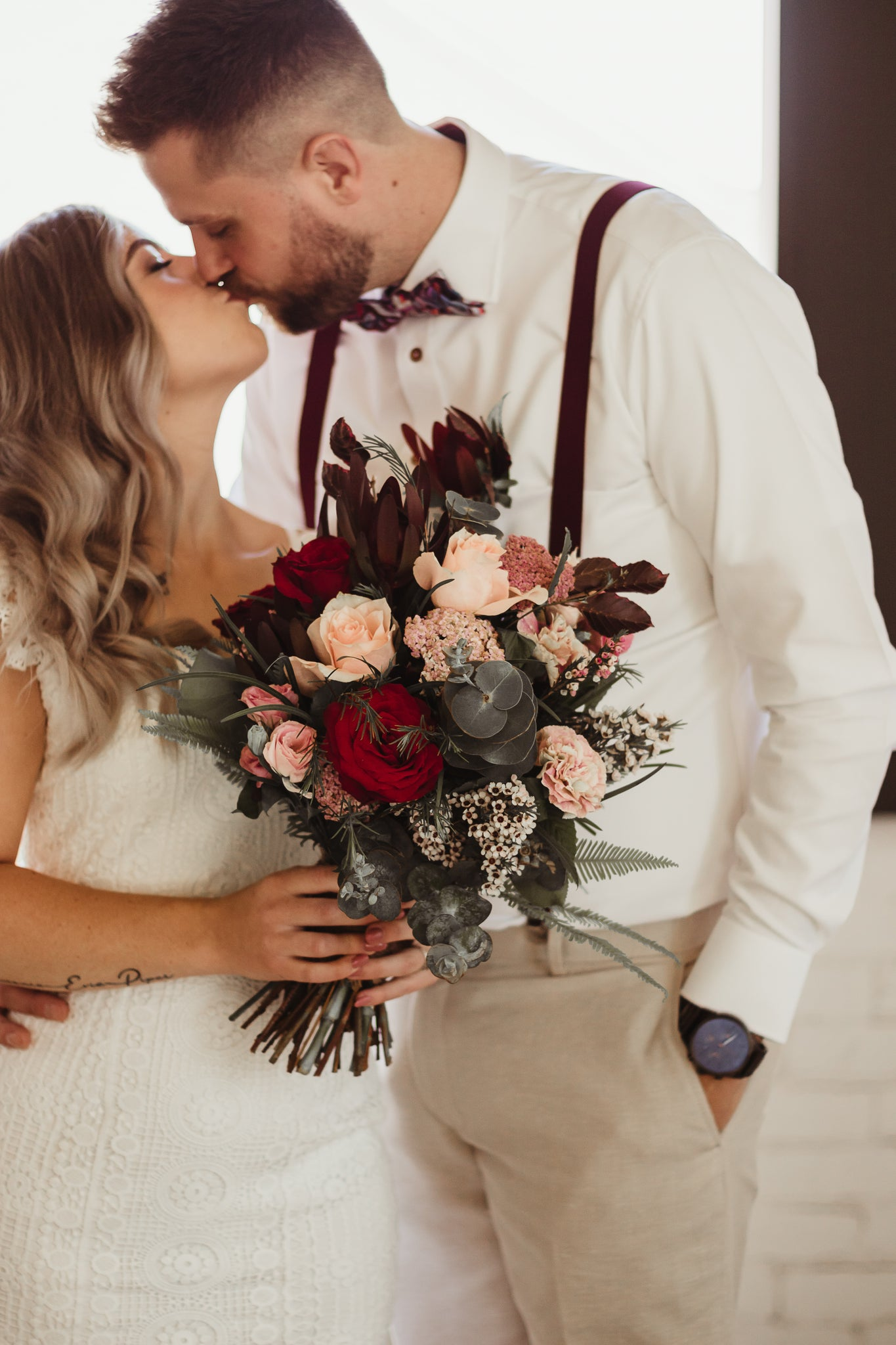 Soon to be Bride and Groom (fiances) kissing before their wedding (a surprise elopement) at The Warehouse venue in Geelong, VIC, Australia. The bride-to-be is holding pink and red flowers.