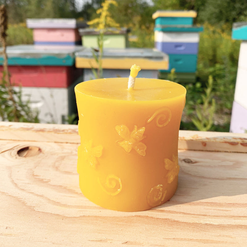 Circular beeswax candle with bee pattern