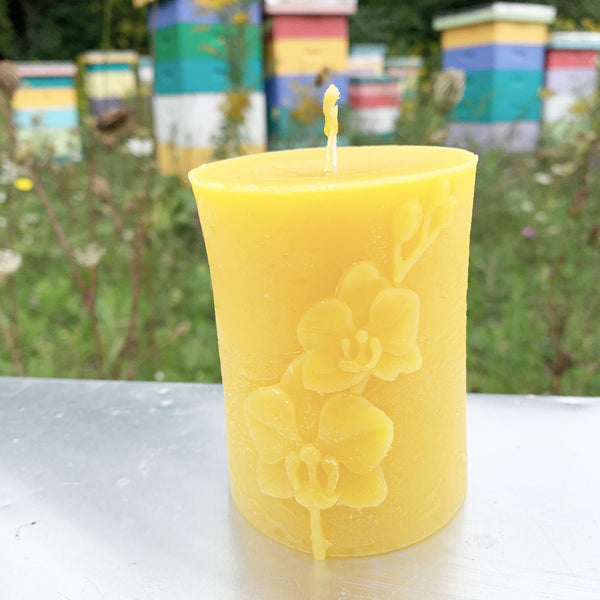 Circular beeswax candle with orchid pattern