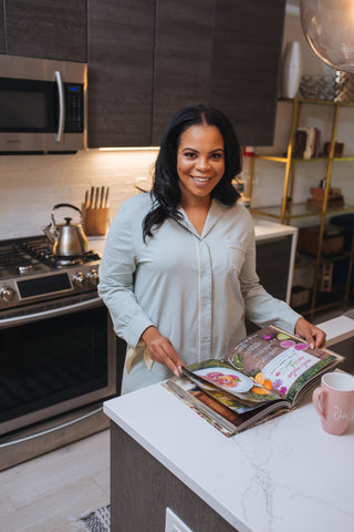Rhea Cherie standing in the kitchen reading a cookbook