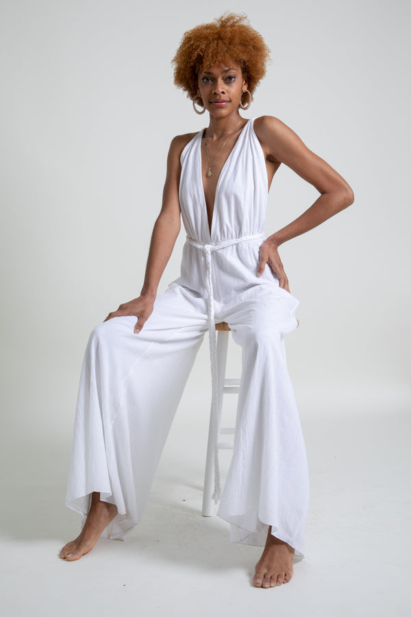 Model is sitting in a white deep v-neck tie around jumpsuit