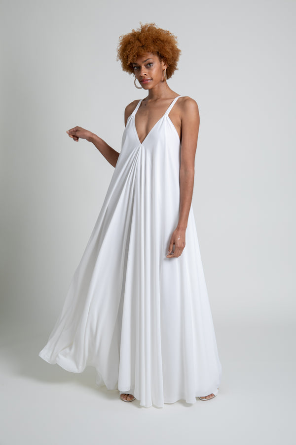 Model is wearing a white crepe floor length flare dress