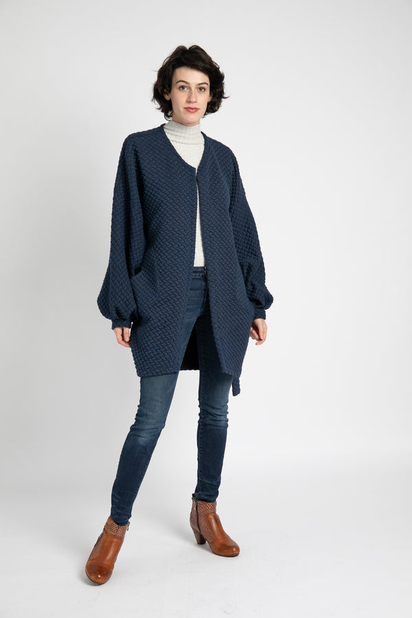 Model is wearing AlekSandraD blue quilted wrap jacket with side patch pockets.