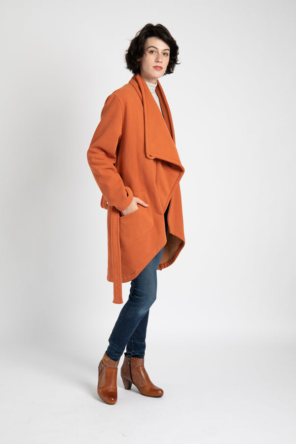 Model is wearing AlekSandraD orange asymmetrical sweatshirt coat.