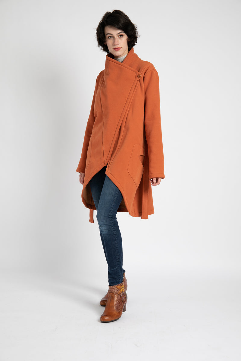 Model is wearing AlekSandraD orange wrap sweatshirt coat.