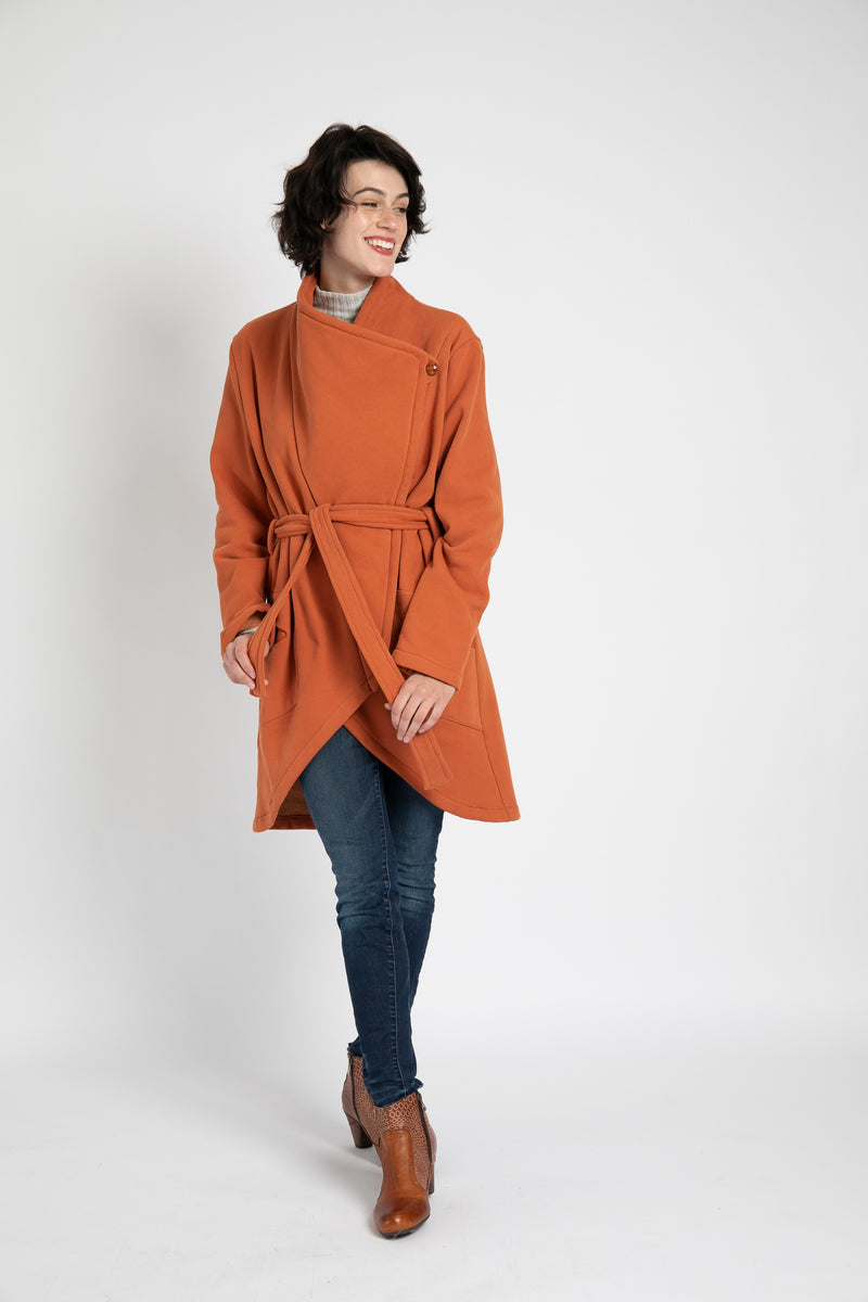 Model is wearing AlekSandraD orange asymmetrical sweatshirt wrap coat.