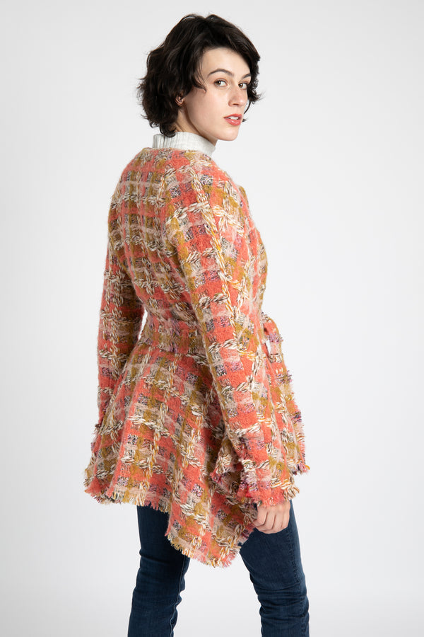 Model is wearing AlekSandraD short pink plaid cashmere coat with self-tie closure.