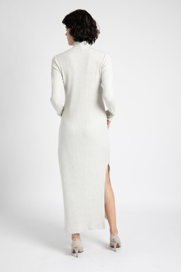 Model is wearing AlekSandraD light gray sweater turtleneck dress with a slit.