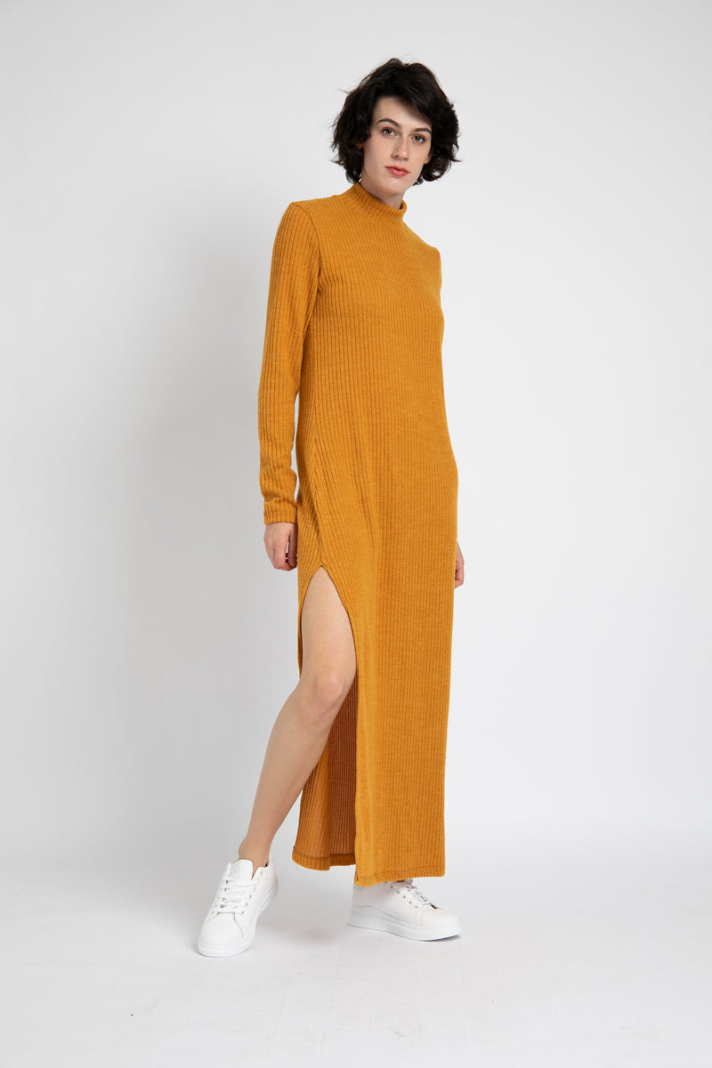 Model is wearing AlekSandraD mustard yellow sweater turtleneck dress with a slit.