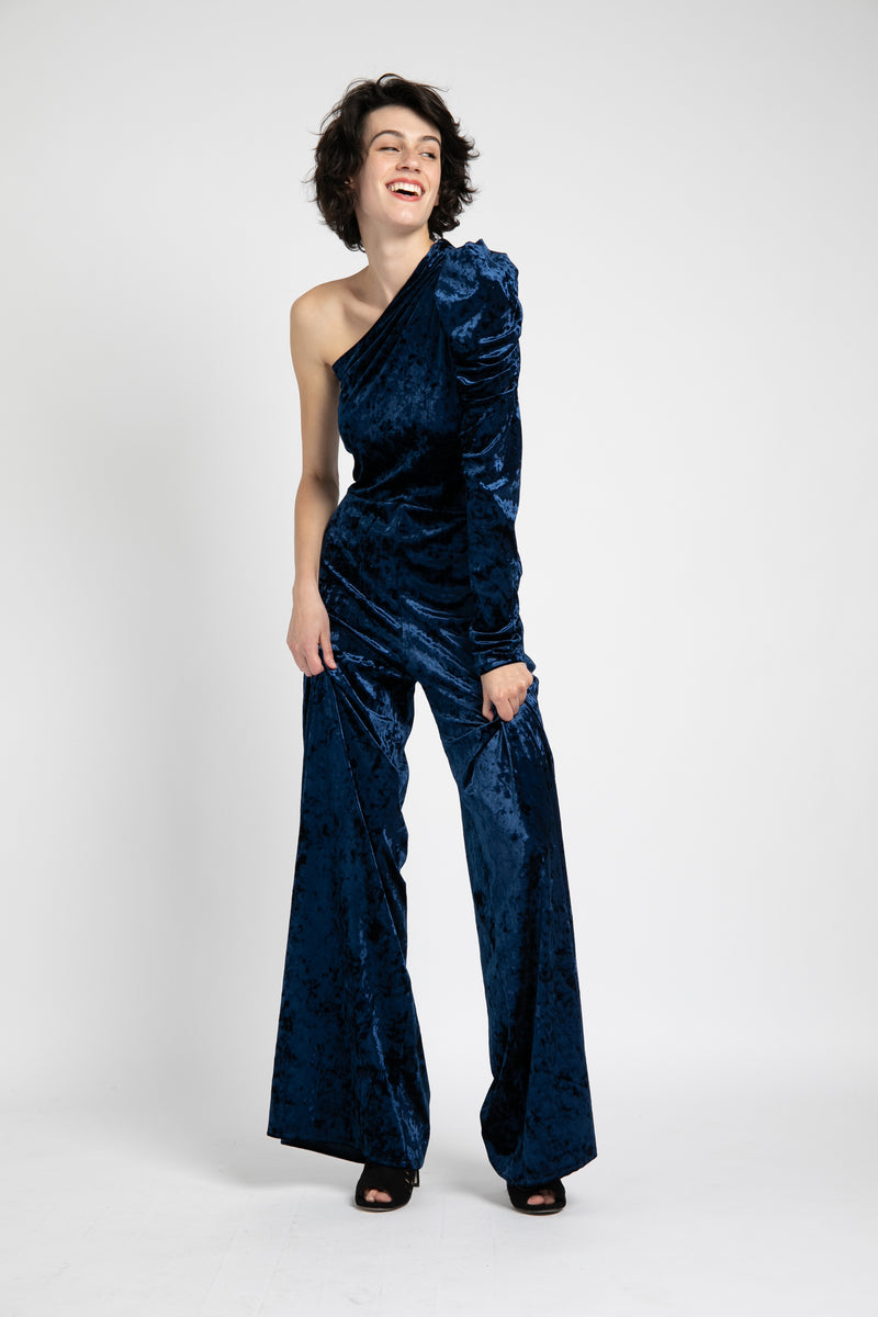 Model is wearing AlekSandraD stretch velvet one shoulder wide leg jumpsuit.