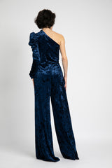 Model is wearing AlekSandraD stretch velvet one sleeve wide leg jumpsuit.