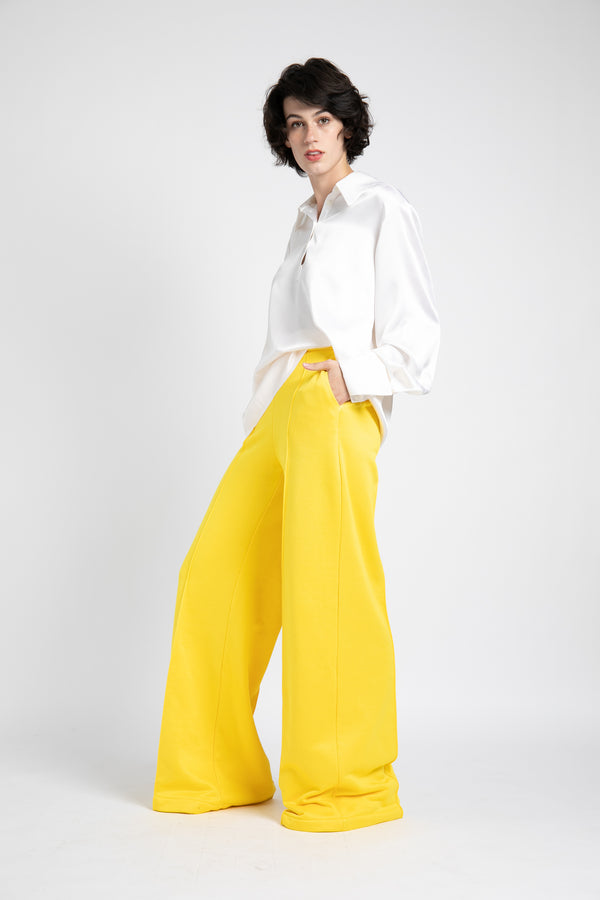 Model is wearing AlekSandraD bright yellow wide leg winter sweatpants.