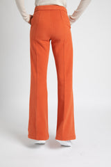 Model is wearing AlekSandraD burnt orange wide leg winter pants.
