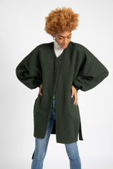 Model is wearing AlekSandraD green quilted wrap jacket with side patch pockets.